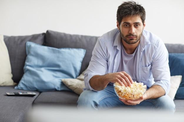 Портрет грустного бородатого мужчины, смотрящего телевизор и держащего миску попкорна, сидя на диване у себя дома