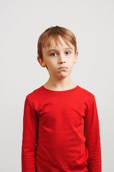Портрет грустного мальчика, стоящего против белой стены. несчастный ребенок смотрит в камеру. эмоции и выражение лица. молодой маленький кавказский ребенок в красной рубашке.