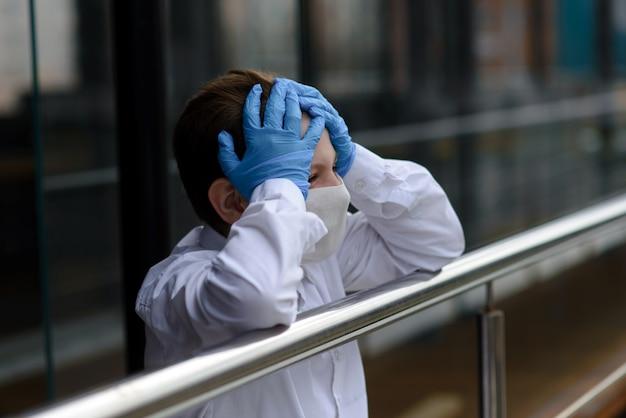 屋外の閉じた遊び場でフェイスマスクで悲しい白人の子供の肖像画。コロナウイルスの社会的距離検疫。