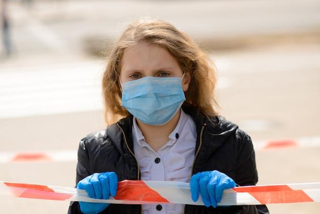 Портрет грустного кавказского ребенка в лицевой маске на закрытой внешней площадке. карантин социальной дистанции от коронавируса.