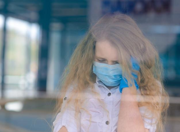 屋外の閉じた遊び場でフェイス マスクで悲しい白人の子供の肖像画。コロナウイルスの社会的距離検疫。