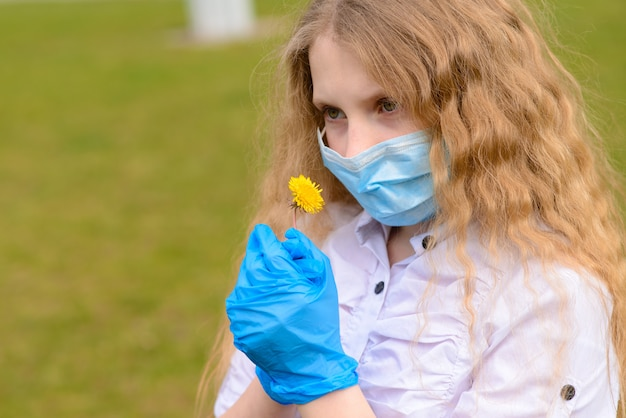 市と屋外の公園でフェイスマスクで悲しい白人少女の肖像画。コロナウイルスの社会的距離検疫。