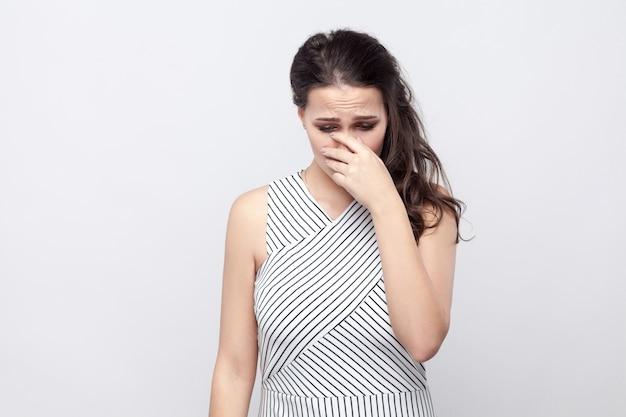 화장과 줄무늬 드레스를 입고 머리를 숙이고 우는 슬픈 우울한 아름다운 젊은 브루네트 여성의 초상화. 실내 스튜디오 촬영, 회색 배경에 고립.