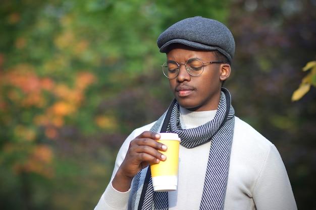 Портрет грустного депрессивного расстроенного расстроенного темнокожего парня, красивого афро-американского молодого человека, идущего в золотом осеннем парке в шляпе, шарфе и очках с чашкой кофе, чувствуя себя плохо, несчастно