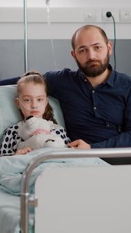 病気の娘の手を握りながらカメラを見ている悲しい家族の肖像画