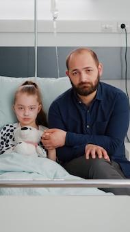 病棟での医療相談中にカメラを覗き込んでいる病気の子供の手を握っている悲しい父親の肖像画。治療を待っている病気の感染後に回復しているベッドに横たわっている若い女の子