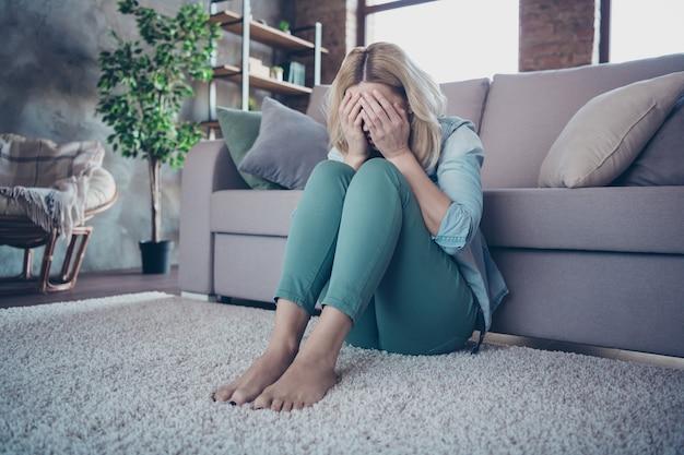 泣いているカーペットの上に座っている悲しい欲求不満のウェーブのかかった髪の女性の肖像画