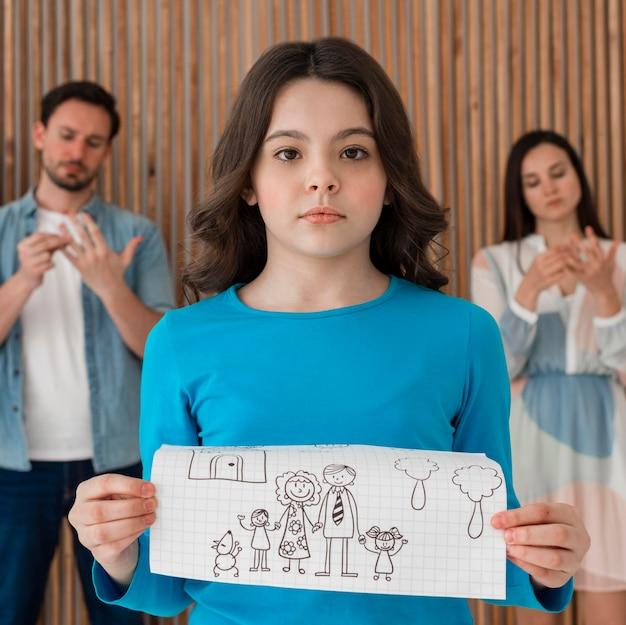 Портрет грустной девушки, держащей семейный рисунок