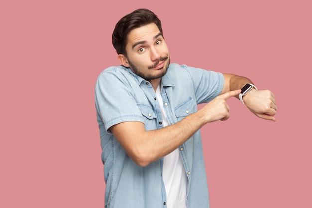青いカジュアルなスタイルのシャツを着て立っている悲しいハンサムなひげを生やした若い男の肖像画は、彼のスマートウォッチを指して見せて、カメラを見ています。ピンクの背景に分離された屋内スタジオショット。