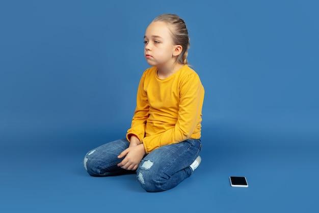 青い背景に孤立して座っている悲しい少女の肖像画。