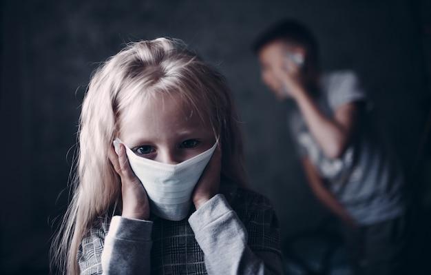 Портрет грустной маленькой девочки в медицинской маске, концепции защиты от вирусов.
