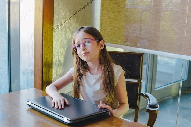 Портрет грустной маленькой девочки с портативным компьютером. расстроенная девушка-подросток на портативном компьютере. компьютер