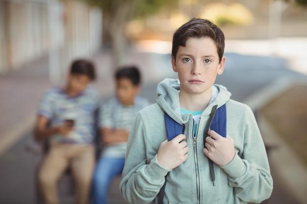 キャンパスでカバン立って悲しい少年のポートレート