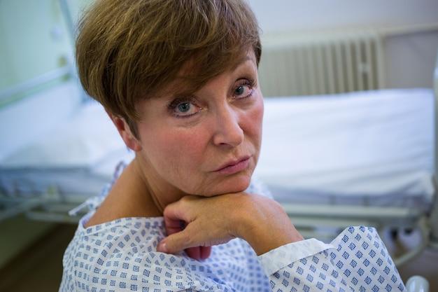 Портрет грустно старшего пациента, сидя на кровати