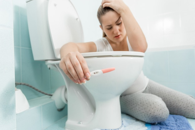 バスルームに座って陽性の妊娠検査を保持している悲しい病気の女性のポートレート