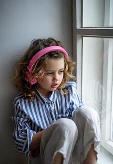 窓枠に座って、自宅の屋内でヘッドフォンを持っている悲しい小さな女の子の肖像画。