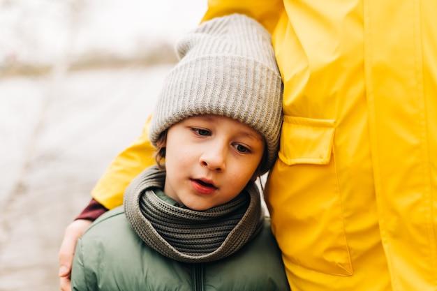 Портрет грустного сына с отцом стоят на берегу озера и держатся за руки счастливой семьей с