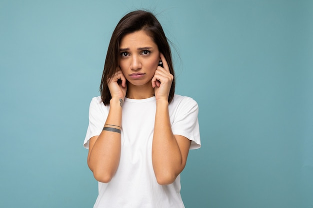 복사 공간이 파란색 배경에 고립되고 손가락으로 귀를 덮는 모형에 대한 캐주얼 흰색 티셔츠를 입고 성실한 감정을 가진 슬픈 슬픈 젊은 꽤 좋은 갈색 머리 여자의 초상화.