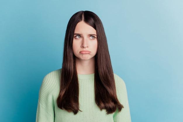 슬픈 불행 한 여자의 초상화는 청록색 배경에 고립 된 빈 공간을 봐