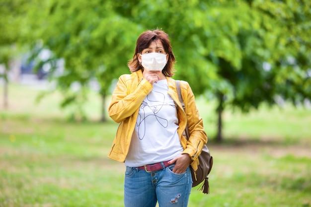 晴れた春の暖かい日に保護用の白い医療マスクで通りでポーズをとって悲しい正体不明の女性の肖像画