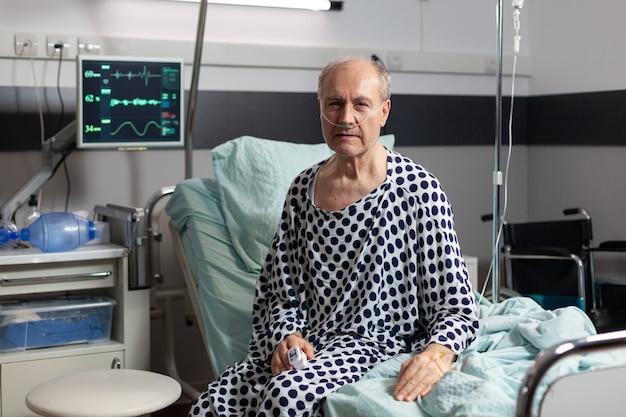 병원 침대의 가장자리에 앉아 슬픈 몸이 좋지 않은 노인의 초상화