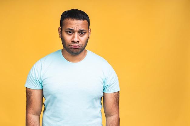 不満の悲しみの顔で立ってカメラを見ている悲しいupdetまたは退屈なアフリカ系アメリカ人の黒人インドの若い男の肖像画。黄色の背景に分離された屋内スタジオショット。