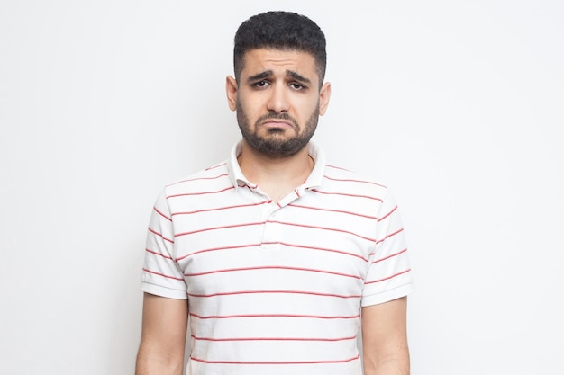 不満の悲しみの顔で立ってカメラを見ている縞模様のtシャツを着た悲しいupdetまたは退屈なひげを生やした若い男の肖像画。白い背景で隔離の屋内スタジオショット。