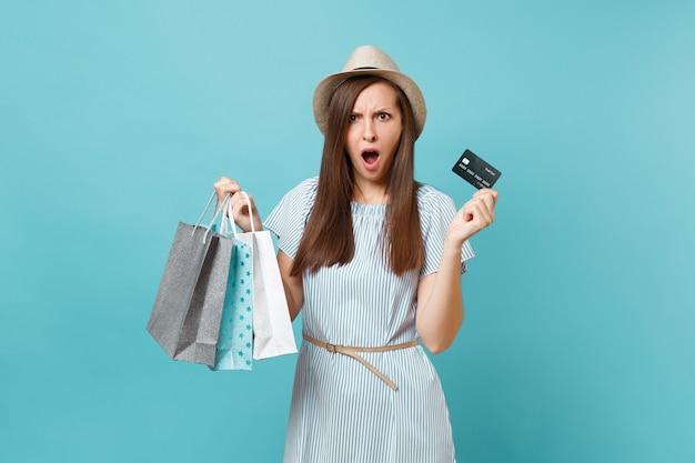 여름 드레스를 입은 슬픈 비명을 지르는 여성의 초상화, 쇼핑 후 구매한 패키지 가방을 들고 밀짚 모자, 파란색 파스텔 배경에 고립 된 은행 신용 카드. 광고 공간을 복사합니다.