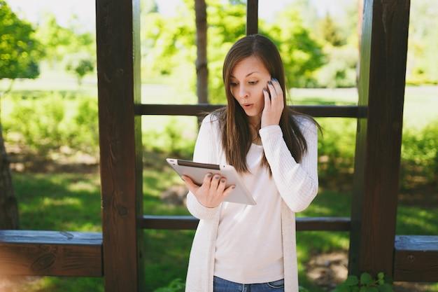 軽いカジュアルな服を着て悲しい動揺ショックを受けた女性の肖像画。タブレットpcコンピューターを保持し、春の緑の自然の屋外の通りにある都市公園で偽のニュースを読んでいるかわいい女の子。ライフスタイルのコンセプト。