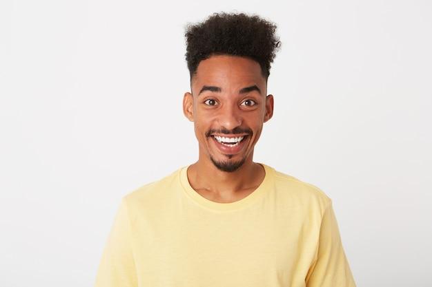 곱슬 머리를 가진 슬픈 화가 젊은 남자의 초상화는 노란색 티셔츠를 입고 우울하고 흰 벽에 고립 된 입술을 커브