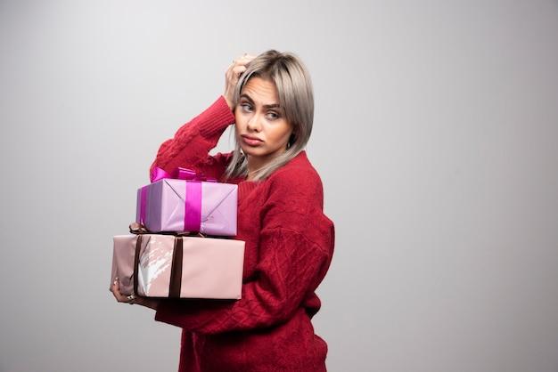 회색 배경에 선물 상자를 들고 있는 슬픈 여자의 초상화.