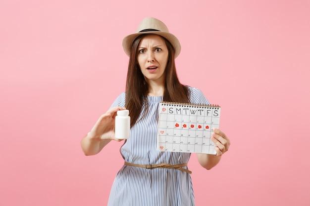 흰색 병을 들고 있는 파란 드레스를 입은 슬픈 여성의 초상화, 여성 기간 달력, 배경에 격리된 월경일을 확인합니다. 의료 의료, 부인과 개념입니다. 공간을 복사합니다.
