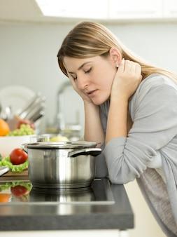 Портрет грустной женщины, опирающейся на стол на кухне