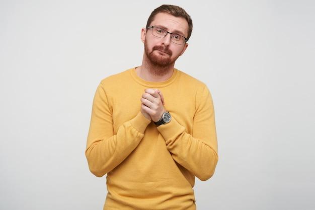 안경에 슬픈 젊은 갈색 머리 수염 난 남자의 초상화는 접힌 입술로 불쌍하게보고 함께 제기 손바닥을 유지, 격리