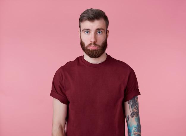 빨간색 티셔츠에 슬픈 젊은 잘 생긴 붉은 수염 문신 된 남자의 초상화, 낮춘 입술로 카메라를보고 불쾌하게 분홍색 배경 위에 선다.