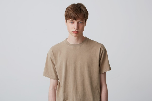 悲しい若い男性の肖像画はベージュのtシャツを着て、白い壁にポーズをとっています。孤立。若い学生は唇を曲げて、悲しい表情をしています