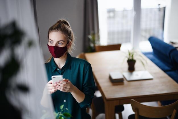 Портрет грустной молодой женщины, использующей смартфон в помещении, концепция коронавируса.