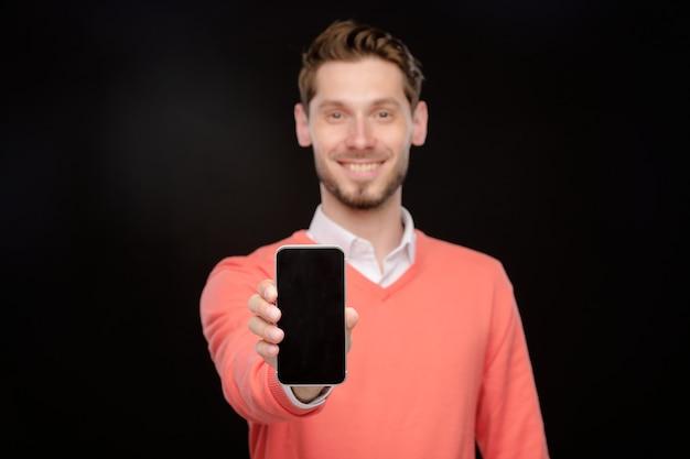새로운 스마트 폰을 제시하고 카메라, 검정색 배경에 보여주는 주황색 스웨터에 영업 관리자의 초상화