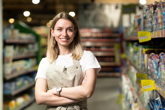 セールスウーマン、笑顔でスーパーマーケットでカメラを見ている女性の肖像画。行の間の店に立っている楽しいフレンドリーな女性の売り手。貿易ビジネスと人々の概念
