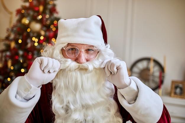 벽난로와 선물 크리스마스 트리 근처 그의 수염을 만지고 안경에 산타 클로스의 초상화.