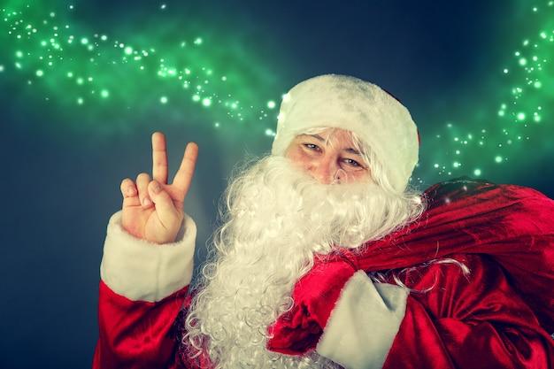 산타 클로스의 초상화입니다. 산타 클로스는 선물 가방을 들고 있습니다. 크리스마스 판타지.