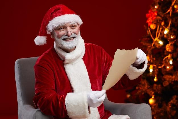肘掛け椅子に座って、クリスマスの手紙を読んで笑っているサンタの肖像画
