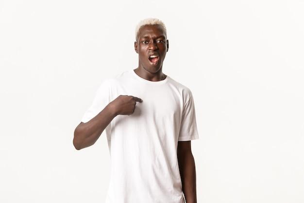 Портрет нахального афро-американского блондина, указывающего на себя и высокомерного ругательства