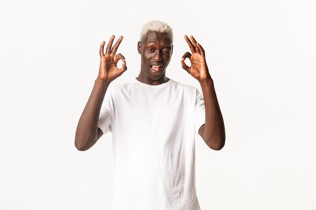 生意気な魅力的なアフリカ系アメリカ人の金髪の男の肖像画、ウィンクし、承認で大丈夫なジェスチャーを示しています