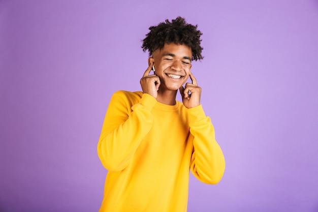 紫色の背景の上に分離されたbluetoothイヤポッドを介して音楽を聴きながら、目を閉じて笑顔のスタイリッシュなアフロ髪型を持っている満足しているアフリカ系アメリカ人の少年の肖像画