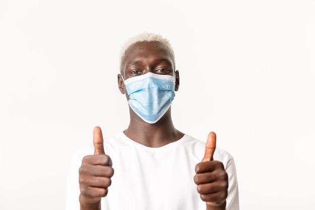 満足しているアフリカ系アメリカ人の笑顔の金髪の男の肖像画、医療マスクを着用し、承認で親指を立てて、褒め言葉を作ったり、誰かを賞賛したりする