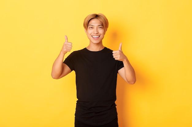 笑顔と黄色の壁に親指を示す満足しているアジア人の肖像画