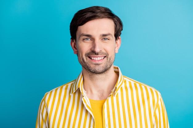 만족한 매력적인 남자의 초상화는 파란 색 배경에 격리된 줄무늬 노란색 셔츠를 입고 카메라를 보며 기분이 좋아 보입니다.