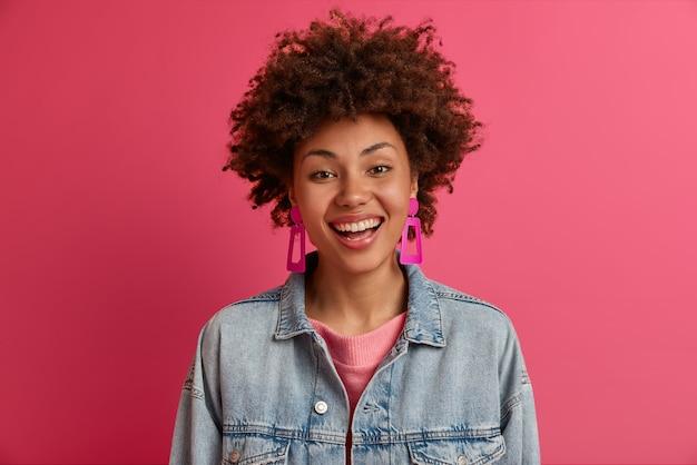 Портрет довольной этнической женщины выглядит с зубастой улыбкой, имеет счастливое настроение, посмеивается над веселой шуткой, одет в модный наряд, чувствует себя беззаботным, изолированным на розовой стене