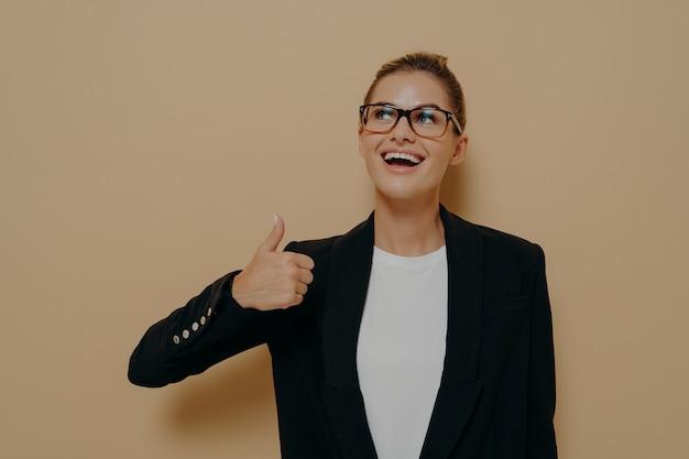 手で親指を表示し、肯定的な表現で逆さまに見ながら笑って、ベージュの背景の上に孤立してポーズをとっている間同意を示す眼鏡で満足している女性の肖像画